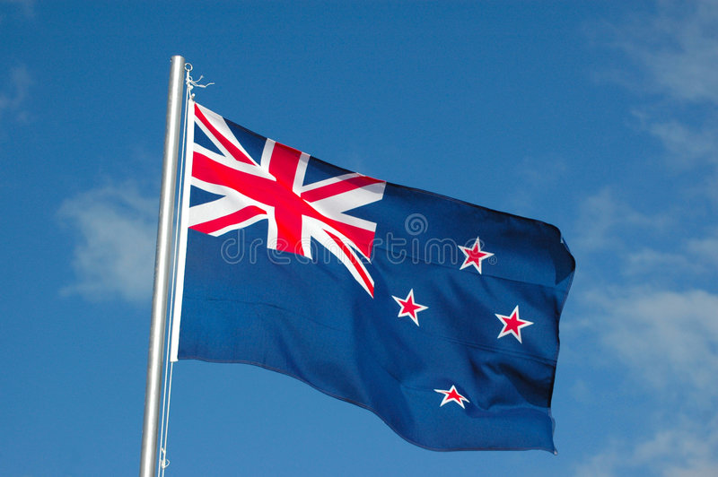 New Zealand flag. The national flag of New Zealand in blue with red and white stars blowing in the wind against a blue sky background
