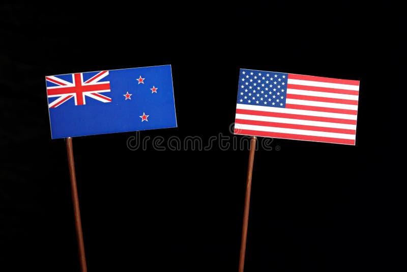 New Zealand flag with USA flag on black. Background royalty free stock photo