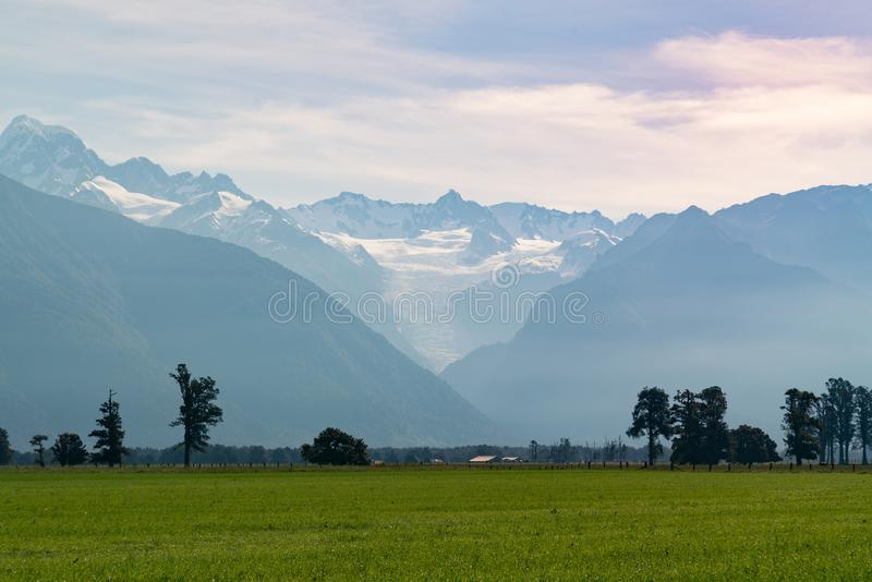 New Zealand Fox glacier bottom view over green glass farm land stock images
