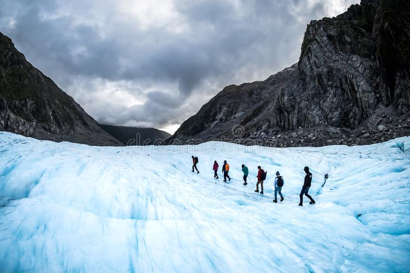 Hikers and travelers walking on ice in Fox Glacier, New Zealand. NEW ZEALAND, FOX GLACIER - MAY 2016: Hikers and travelers walking on ice in Fox Glacier, New stock photography
