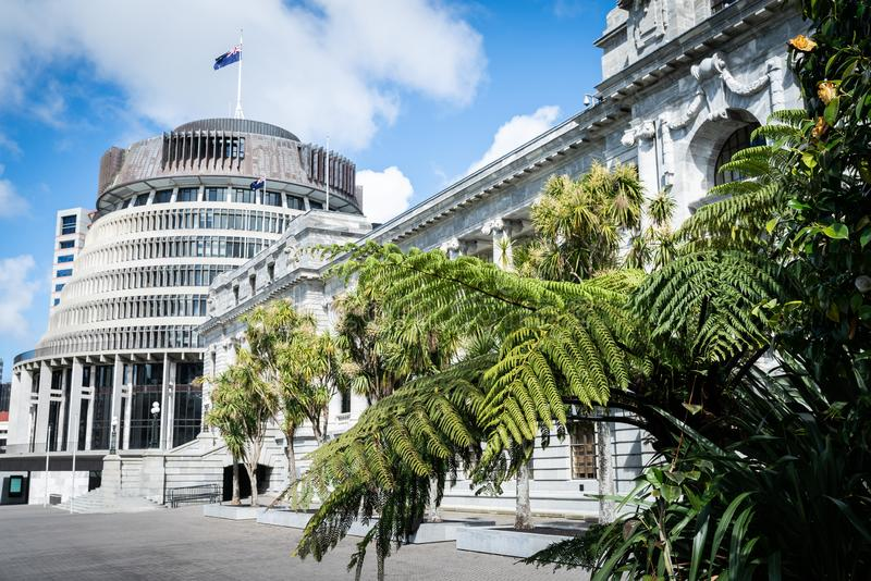 New Zealand Government buildings. House neo classical style House of Parliament with Beehive behind with iconic ponga fern frond one of NZ`s emblems royalty free stock photos