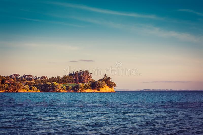 New Zealand iconic landscape - llush green of the trees and cliff over blue sea. New Zealand iconic landscape - llush green of the trees and cliff over blue sea stock photo