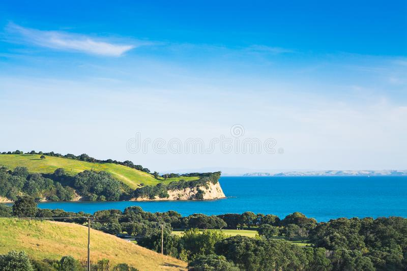 New Zealand iconic landscape - lush green hills and cliff over blue sea. Shakespear regional Park, Auckland stock photography