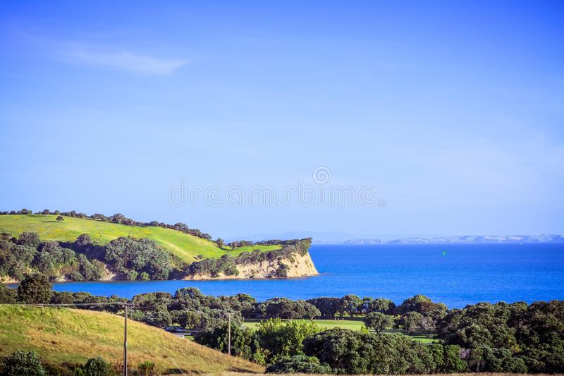 New Zealand iconic landscape - lush green hills and cliff over blue sea. Shakespear regional Park, Auckland royalty free stock photo