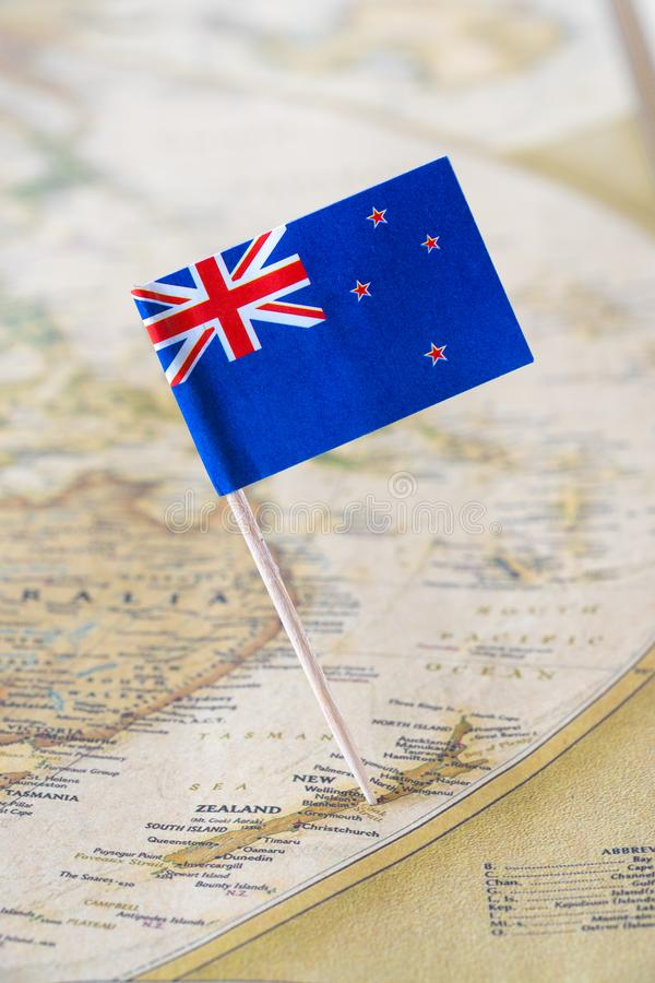 New Zealand map and flag pin. New Zealand paper flag pin on a map, world globe background stock photography