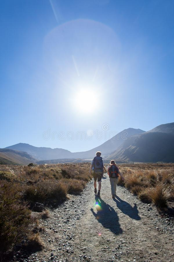 New zealand mountain crossing travel hike. New Zealand hilly mountains travelling travel with your partner and enjoying life, sun on horizon, backpack, wander royalty free stock photos