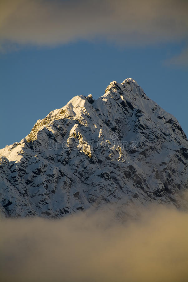 New Zealand Mountains. The tip of a mountain peaks through the clouds as the last rays of light hit the summit royalty free stock images