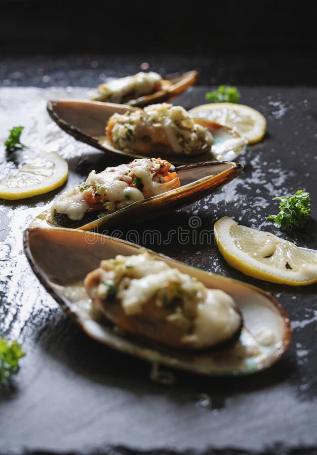 New Zealand Mussels baked with butter, garlic, parsley and cheese stock image