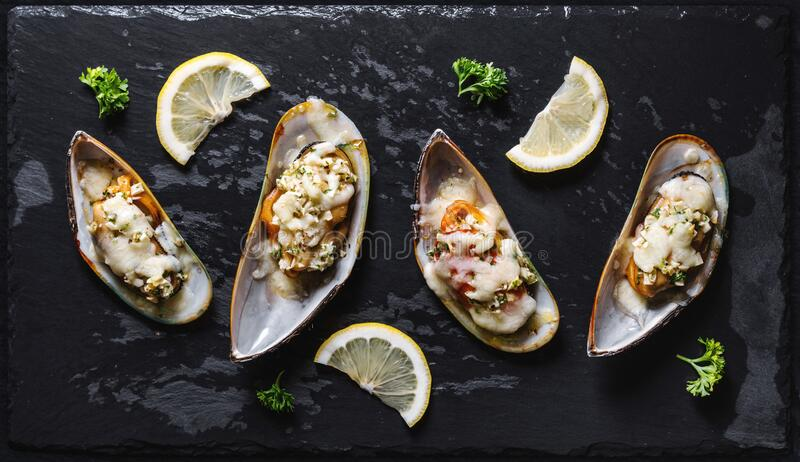 New Zealand Mussels baked with butter, garlic, parsley and cheese royalty free stock photo