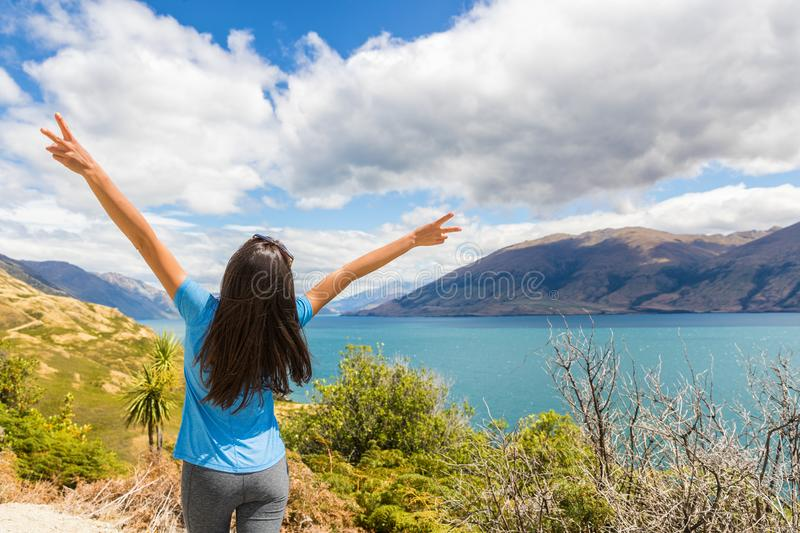New Zealand travel happy tourist woman with arms up at Wanaka lake nature landscape outdoors. Wanderlust adventure young girl with. Peace hand sign royalty free stock photo
