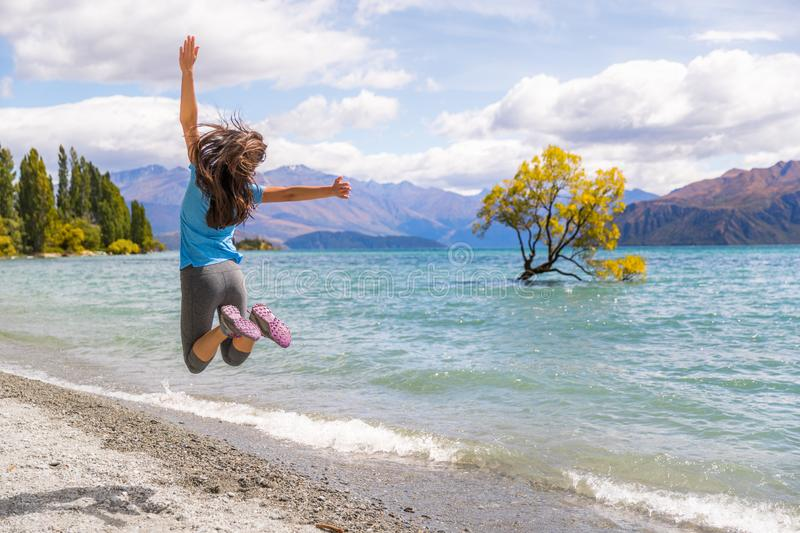 New Zealand travel happy tourist woman jumping of joy at Wanaka lake landscape with lone tree, famous attraction royalty free stock photos