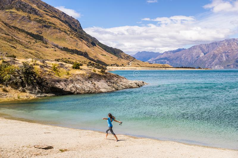 New Zealand travel happy tourist woman running of joy and freedom at beach shore of lake Hawea nature landscape. Near Wanaka, royalty free stock photography