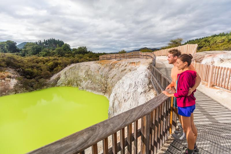 New Zealand travel tourists looking at green pond. Tourist couple enjoying famous attraction on North Island, geothermal pools at stock photo