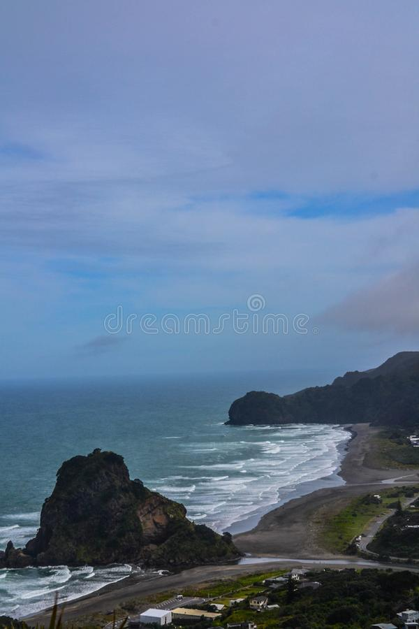 Piha Beach with Lion Rock, New Zealand. New Zeland iconic, famous beaches concept. Panoramic scenic landscape view of surfers popular Piha Beach and Lion Rock in royalty free stock images