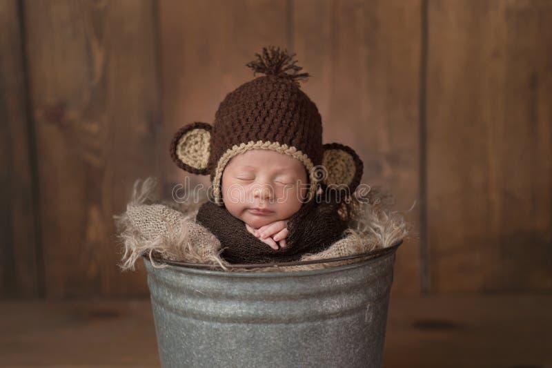 Newborn ребёнок нося шляпу обезьяны стоковые фотографии rf