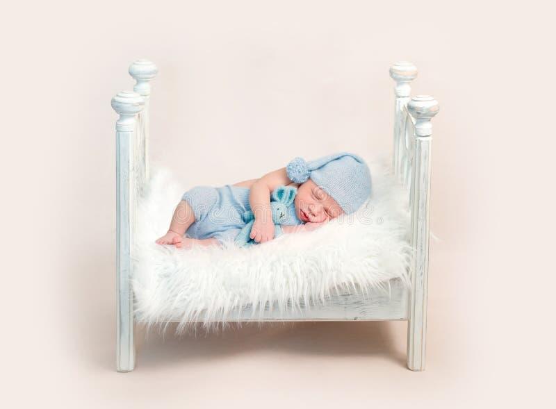 Newborn мальчик в голубом обмундировании спать на шпаргалке стоковые фотографии rf