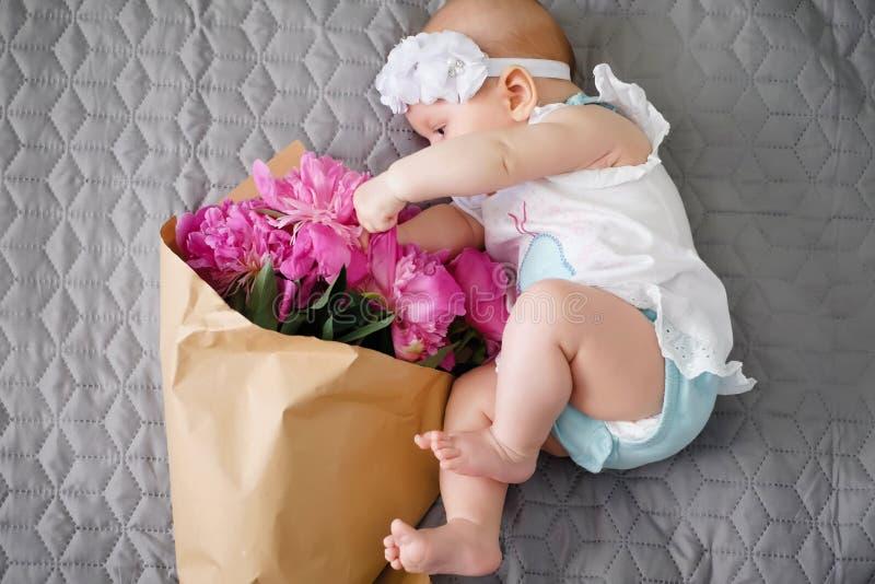 Newborn младенец исследует мир и играть с букетом цветков стоковые фотографии rf