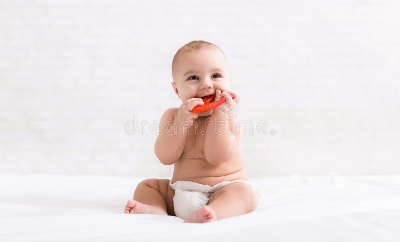 Newborn младенец сдерживая красное teether в кровати стоковые изображения rf