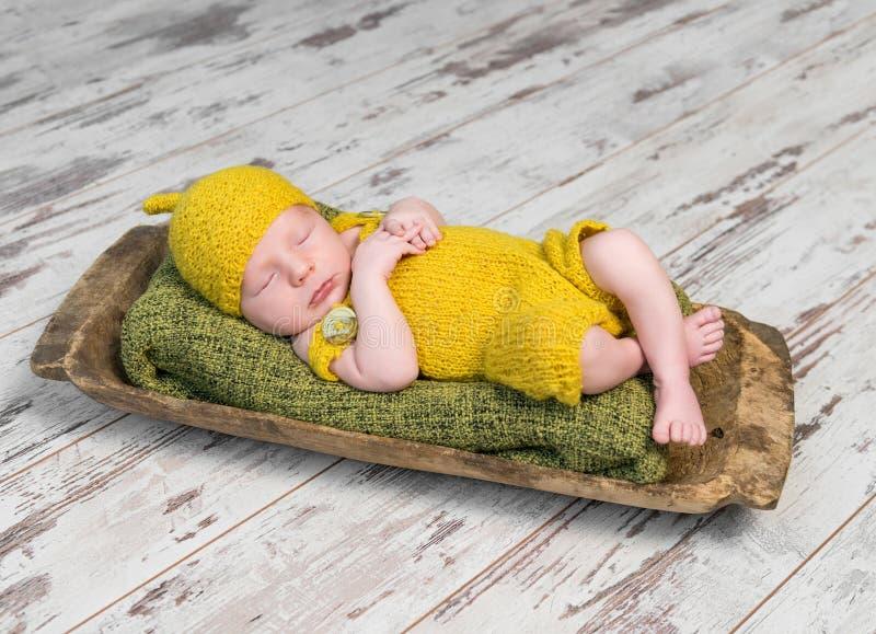 Newborn младенец в желтом костюме спать на деревянной кроватке стоковая фотография