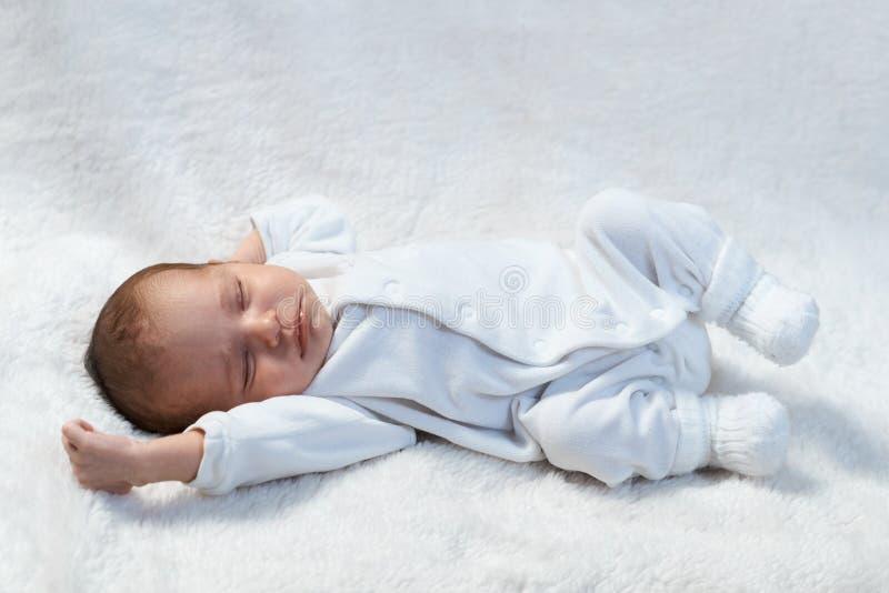 Newborn младенец спать на белом мехе в солнечном свете стоковые изображения