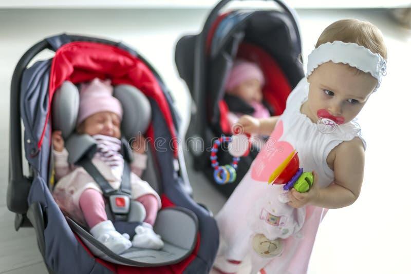 Newborn младенец дублирует девушку сидя в автокресле стоковые изображения