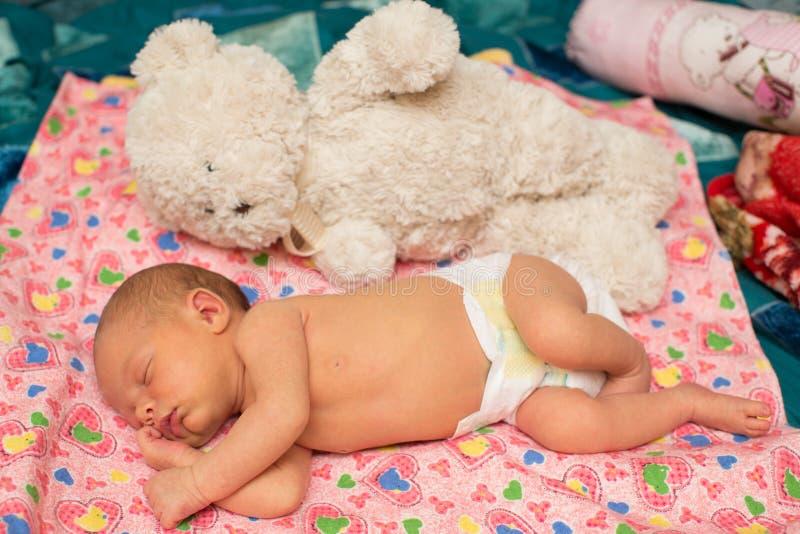 Newborn ребёнок спит с игрушкой на кровати стоковая фотография rf