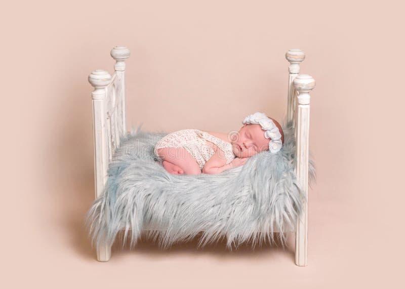 Newborn сон ребёнка на кровати стоковое фото rf