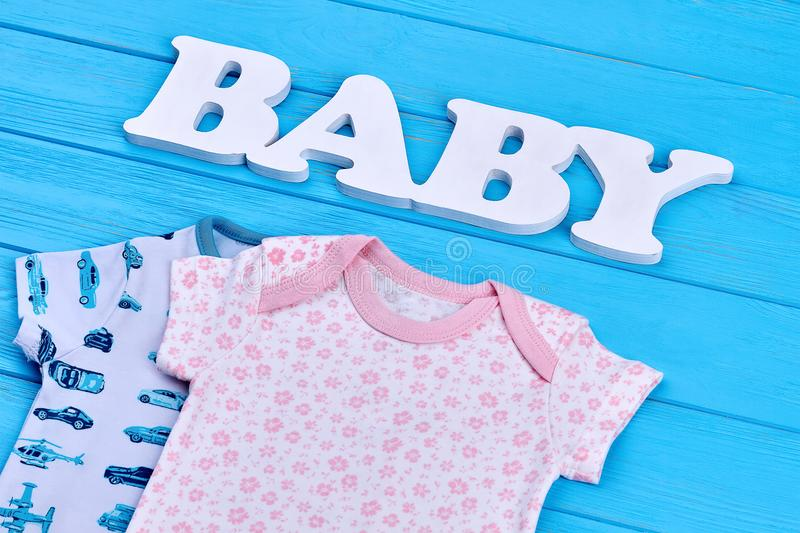 Newborn babies cotton summer outfit. High quality infant childs natural apparel, text baby, blue wooden background stock photos