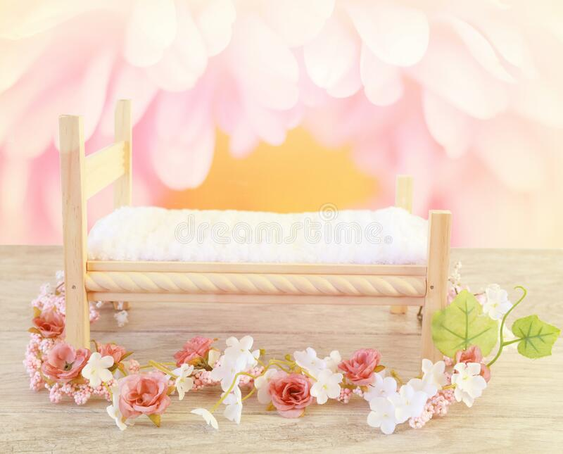 A newborn baby bed prop with flowers and soft pink colors. Newborn bed prop on a wood floor with pink flowers and a white bedspread.  A beautiful photographer`s stock photos