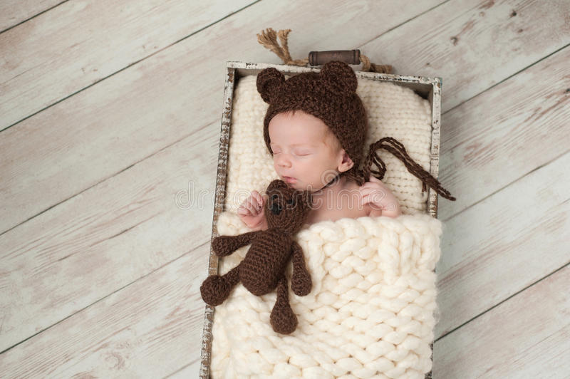 Newborn Baby Boy with Bear Hat and Stuffed Bear Toy. Two week old newborn baby boy wearing a brown, crocheted, bear bonnet and holding a matching Teddy Bear. He royalty free stock image