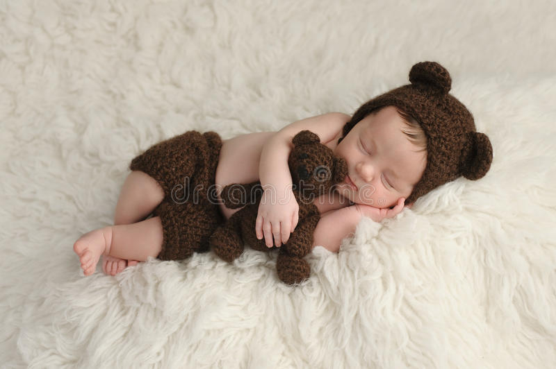 Newborn Baby Boy with Bear Hat and Toy. Three week old newborn baby boy wearing a brown, crocheted bear hat and shorts. He is sleeping on a white flokati rug and stock photos