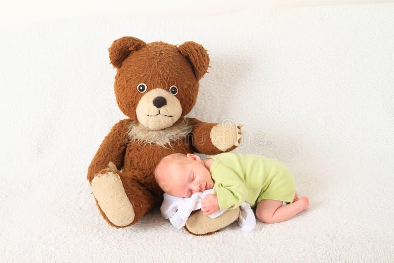 Newborn baby boy sleeping on Teddy bear royalty free stock photography