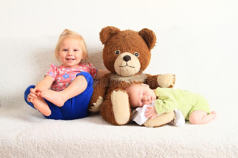 Newborn baby boy with little sister and Teddy bear royalty free stock photos