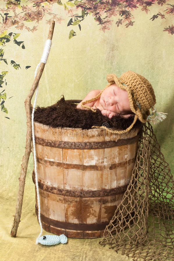 Newborn Baby Boy with Fishing Hat and Pole. 7 day old newborn baby boy sleeping in an old, weathered wooden bucket. He is wearing a crocheted fishing hat and has stock photography