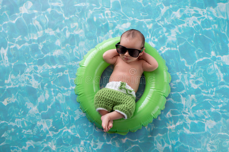 Newborn Baby Boy Floating on a Swim Ring. Two week old newborn baby boy sleeping on a tiny, green, inflatable swim ring. He is wearing green, crocheted board stock images