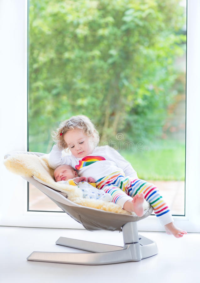 Newborn baby boy and his sister relaxing in swing. Newborn baby boy and his toddler sister relaxing in a swing next big window into garden royalty free stock photo