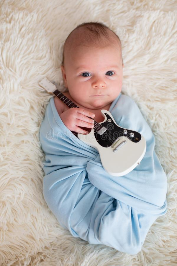 Newborn baby boy, holding a little guitarand smiling stock photos