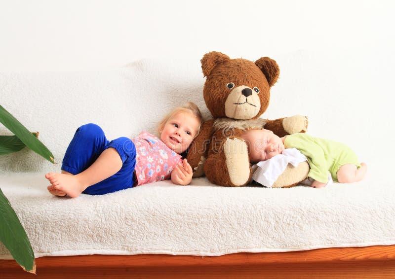Newborn baby boy with little sister lying on Teddy bear stock photos