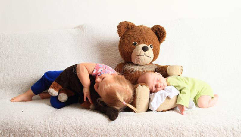 Newborn baby boy with little sister sleeping on Teddy bear royalty free stock image