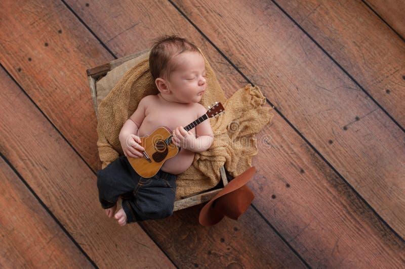 Newborn Baby Boy Playing a Tiny Guitar stock photos