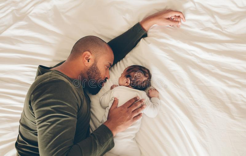 Newborn baby boy sleeping with his father on bed royalty free stock images