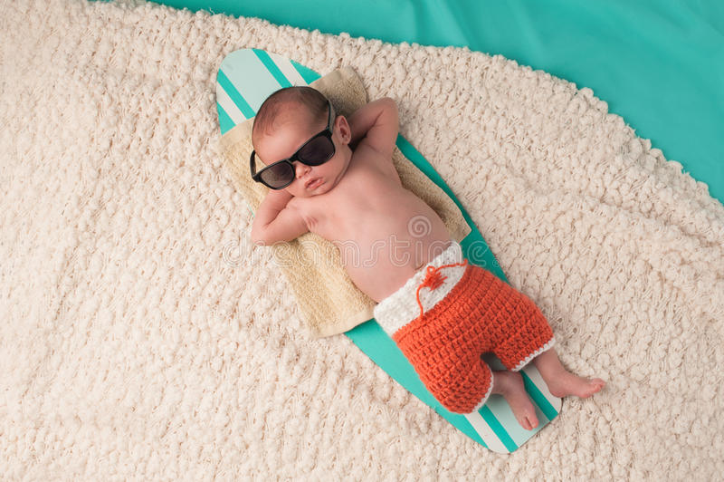 Newborn Baby Boy Sleeping on a Surfboard. Newborn baby boy sleeping on a tiny surfboard. He is wearing black sunglasses and crocheted boardshorts royalty free stock photo