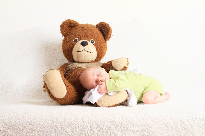 Newborn baby boy sleeping on Teddy bear stock photos