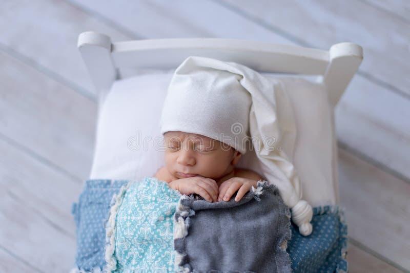 Newborn Baby Boy Sleeping on a Tiny Bed stock image