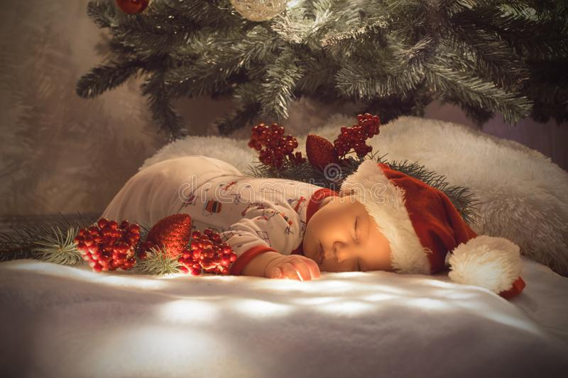Newborn baby boy sleeping under Christmas tree near lot of decorations. Wearing Santa´s hat stock photography
