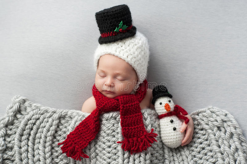 Newborn Baby Boy with Snowman Hat and Plush Toy. Two week old, newborn, baby boy wearing a crocheted snowman bonnet and scarf. He's holding a matching plush toy royalty free stock photography
