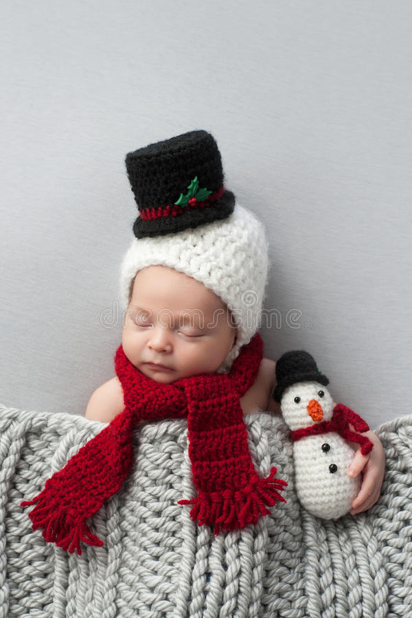 Newborn Baby Boy with Snowman Hat and Plush Toy. Two week old, newborn, baby boy wearing a crocheted snowman bonnet and scarf. He's holding a matching plush toy stock photography