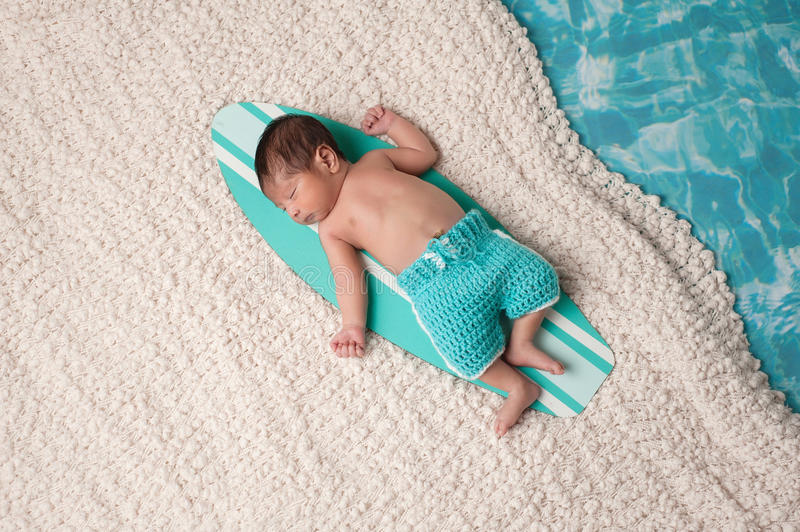 Newborn Baby Boy on Surfboard. Eleven day old newborn baby boy sleeping on a tiny, turquoise blue and white surfboard. He is wearing aqua colored, crocheted royalty free stock image
