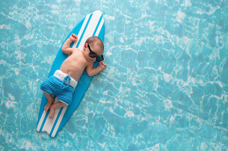 Newborn Baby Boy on Surfboard. Two week old newborn baby boy sleeping on a tiny, light blue and white surfboard. He is wearing light blue, crocheted board shorts royalty free stock photos