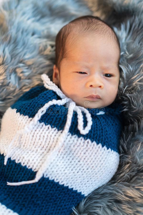 Newborn baby boy swaddled in a knit wrap on fur bed royalty free stock photo